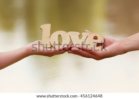 hands of man and woman hold word love