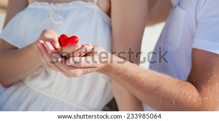 Hands of man and woman holding red heart protecting it together - stock photo