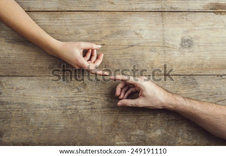 Hands of man and woman touching tenderly. Studio shot on a wooden background, view from above.