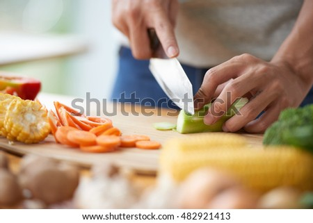 Hands of man cutting celery for soup or salad