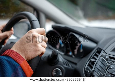 hands of man driving the car and holding wheel