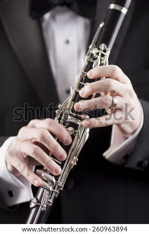 hands of man in tuxedo holding clarinet, room for copy - stock photo