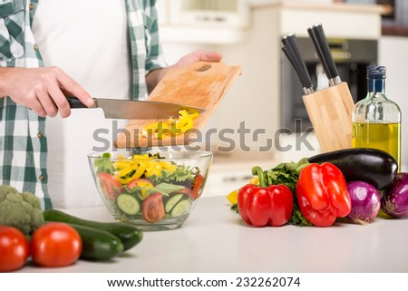 Hands of man is cooking vegetable salad in the kitchen. - stock photo