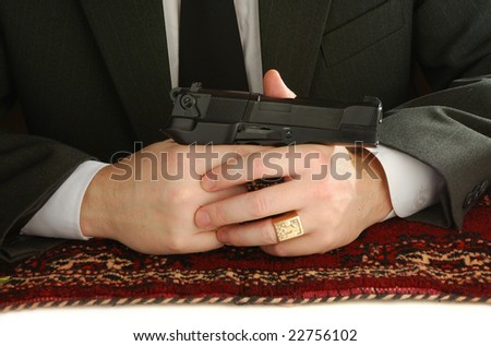 hands of man on an east carpet with a pistol