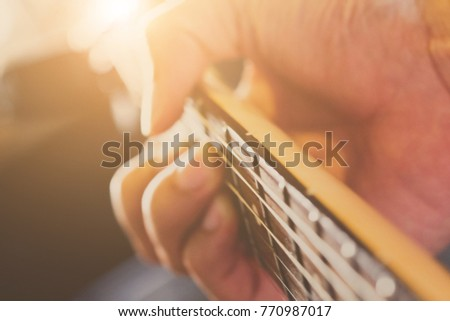 Hands of man playing electric guitar close up