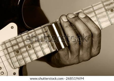 Hands of man playing electric guitar. Guitarist hands. Fingers with metallic slider pressing strings on maple fretboard closeup sepia tint. Old looking style. - stock photo