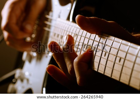 Hands of man playing electric guitar. Low key photo. - stock photo