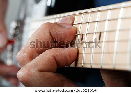 Hands of man playing electric guitar with red pick closeup