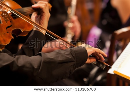 Hands of man playing the violin in the orchestra in dark colors