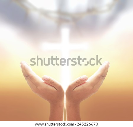 Hands of man praying over blurred crown of thorns and the white cross on a sunset. - stock photo