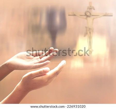 Hands of man praying over blurred Jesus on the cross and glass of wine and Loaf of bread in eucharist of christian. Mercy Reconcile Glorify Redeemer Last Supper Maundy Thursday Corpus Christi concept - stock photo