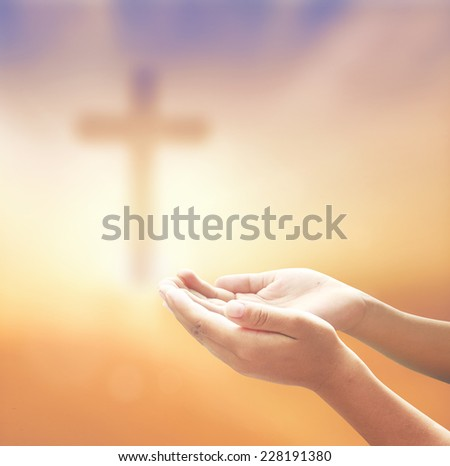 Hands of man praying over blurred the cross on a sunset. - stock photo
