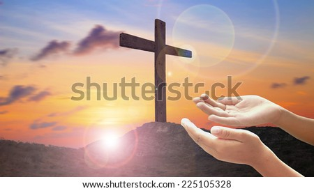 Hands of man praying over the cross on the mountain golgotha representing the day of christs crucifixion in a sunset. - stock photo