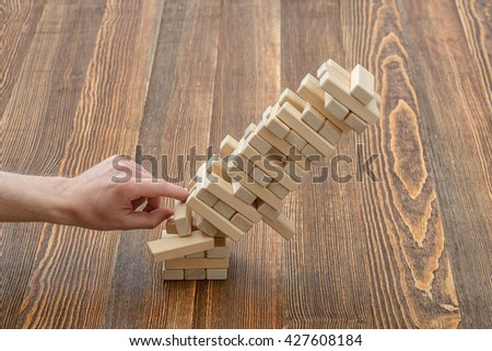 Hands of man pushed the brick and destroyed the tower. Janga. Close-up photo. Imbalance. Collapse and destruction. Mistake. Entertainment activity. Game of physical and mental skill. Removing blocks - stock photo
