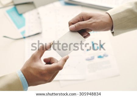 Hands of manager giving blank business card to his partner - stock photo