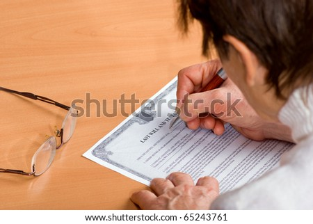 Hands of mature woman signing Last Will sitting on desk - stock photo