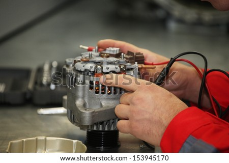 Hands of mechanic restores a generator - stock photo