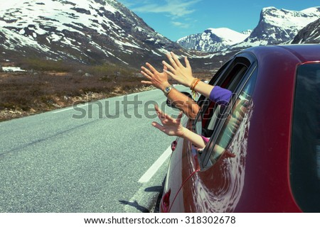 hands of men and children peering out of the car on a background of mountains