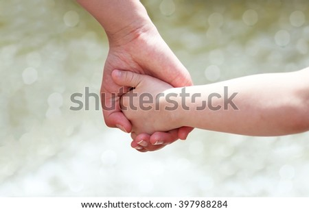 Hands of mother and child - stock photo