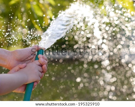 Hands of mother and child Help plants. watering plants in garden - stock photo