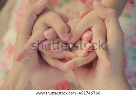Hands of mother and child together. Mother and child holding hands (vintage) - stock photo