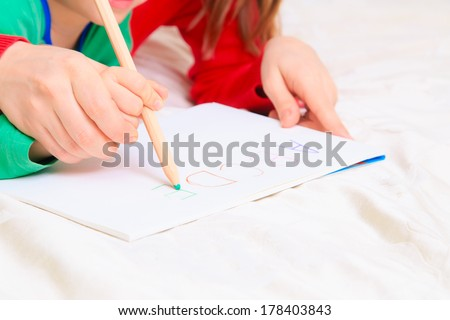 hands of mother and child writing letters, early education