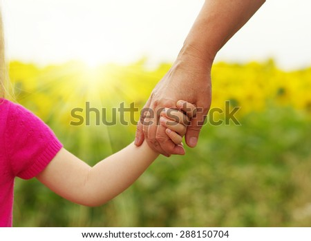Hands of mother and daughter holding each other on field - stock photo