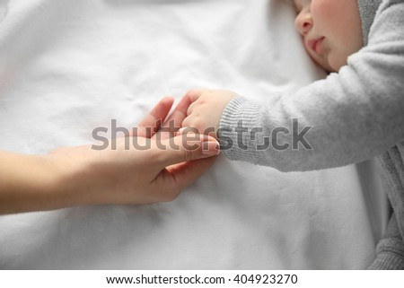 Hands of mother and her little baby boy on the bed, close up - stock photo