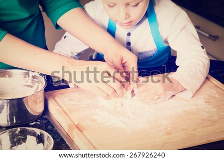 hands of mother and son kneading dough on wooden table - stock photo