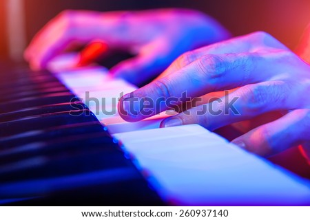 hands of musician playing keyboard in concert with shallow depth of field - stock photo