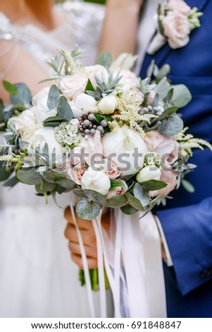 Hands of newlyweds with rings and wedding bouquet