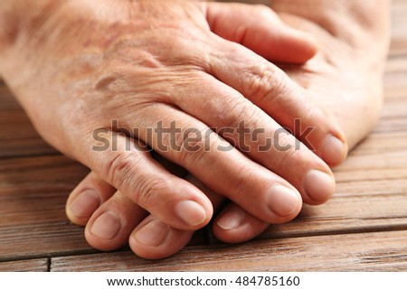 Hands of old senior on a wooden table