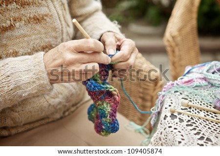 hands of old woman knitting wool, close up - stock photo