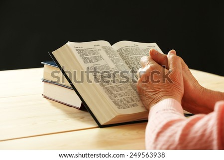 Hands of old woman with Bible on table and dark background - stock photo