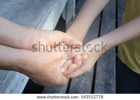 Hands of older woman holding the hand of a younger woman.