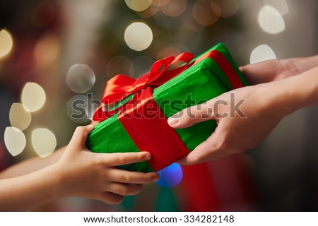 Hands of parent giving a Christmas gift to child. - stock photo