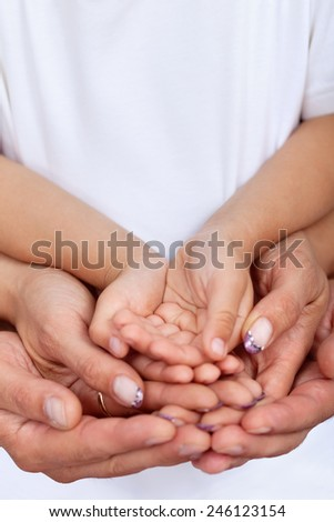 Hands of parents and child holding something together