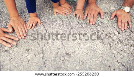 Hands of parents with their kids laid on the ground - stock photo