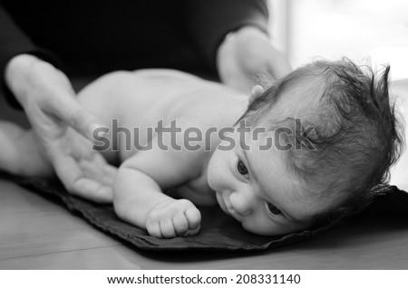 Hands of pediatrician nurse checks infant baby body development examination. (BW) - stock photo