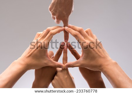 Hands of people forming a symbol of peace - stock photo