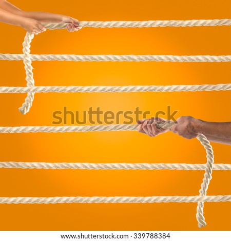 Hands of people pulling the rope on orange background.   - stock photo