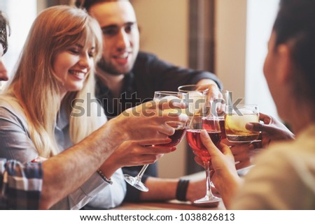 Hands of people with glasses of whiskey or wine, celebrating and toasting in honor of the wedding or other celebration.