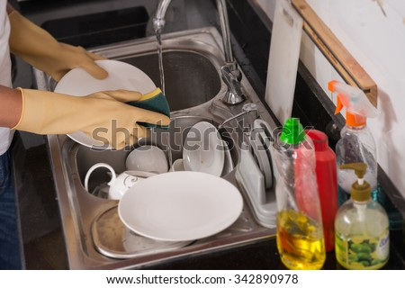 Hands of person washing plates with detergent - stock photo