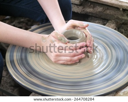 Hands of potter do a clay pot  - stock photo