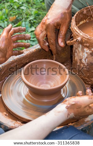 Hands of potter, potter's wheel