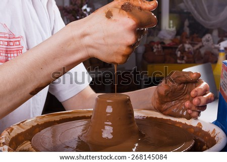 hands of potter working  with clay on pottery wheel - stock photo