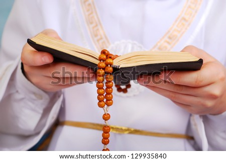hands of praying boy going to the first holy communion holding prayer book and wooden rosary - stock photo