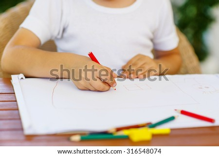 Hands of preschool kid boy  making homework. Little child painting with colorful pencils, indoors. School, education concept - stock photo