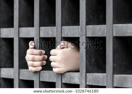 Hands of prisoner gripping on black wooden prison bars. (Selective Focus)