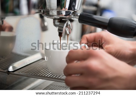 Hands of professional barista holding two white cups on the grating of coffee machine looking how coffee pouring into them - stock photo
